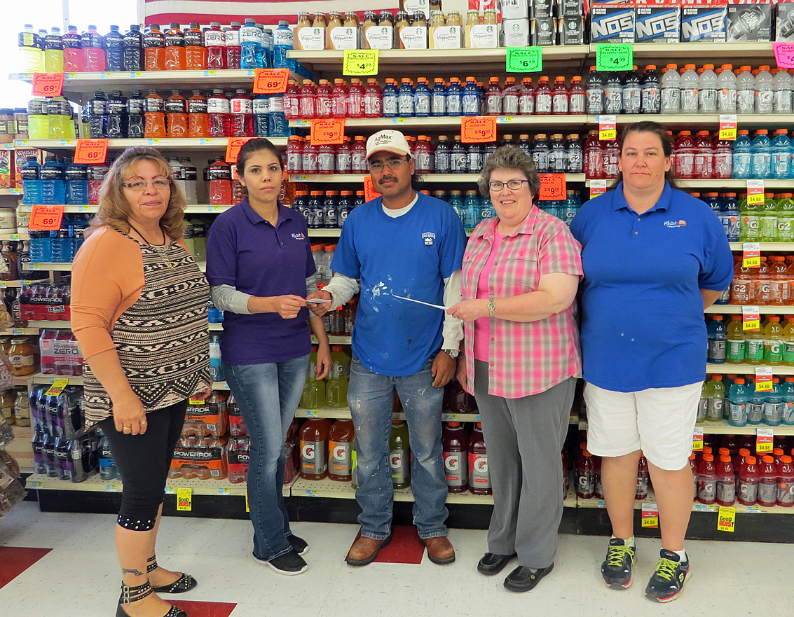 Super Dad 2015 Sergio Hermosillo accepts his Father's Day honors from Chamber Director Ruth Van Horn in the pink shirt. Also congratulating Sergio are White's Foodliner employees, Patricia Fabela and Claudia Alvarado. White's employee Cindy Rivera is at far right. Former White's manager Dean Van Horn is not pictured, as he is already working in Nebraska.