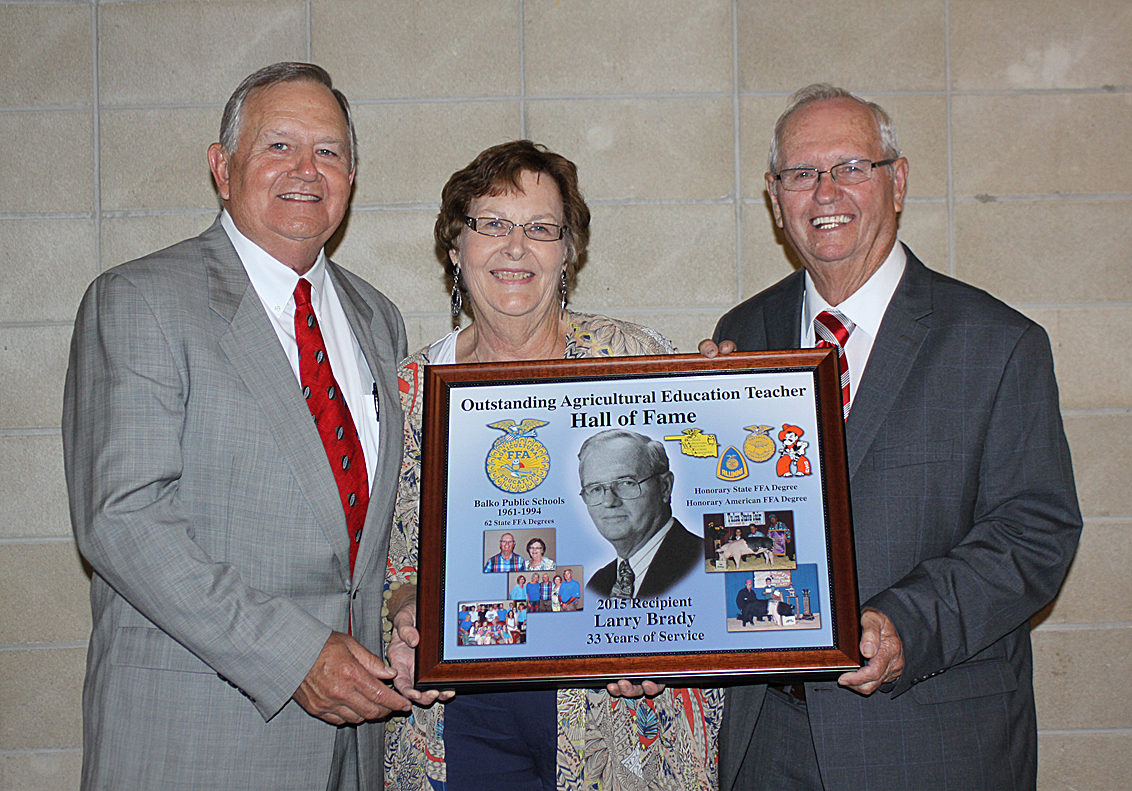 Oklahoma State FFAAdvisor Jack Staats  presents Larry Brady with a Hall of Fame plaque during the ceremony Tuesday, August 4 acknowledging Larry's 33 years of service as an Ag teacher in Balko, Ok. Larry's wife Nelda stands beside her husband.