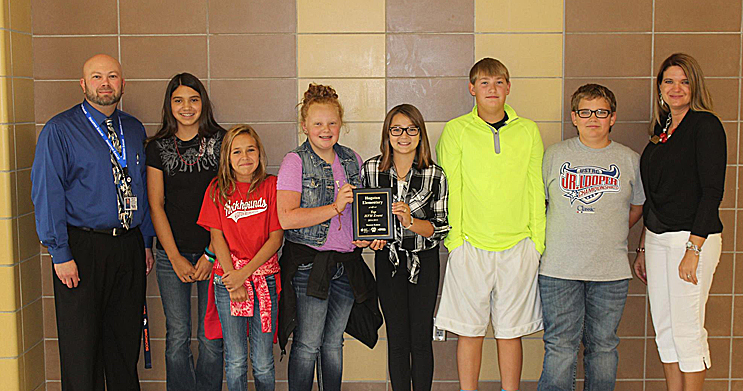 Hugoton Intermediate Principal Larry Lyder, along with several Hugoton Elementary students, accepts the Hoops for Heart plaque in recognition of their significant contribution to the American Heart Association through last year's Hoops for Heart event. From left to right are Principal Lyder, Alexa Sanchez, Cami Maravilla, Taylor Grubbs, Breckyn Haar, Cade  Mecklenberg, Cutter Hawks and Jennifer Thompson, Senior Youth Director for Western Kansas for the American Heart  Association. Congratulations HES Kids and event coordinator Ms. Terri Daniels - Great Job!!