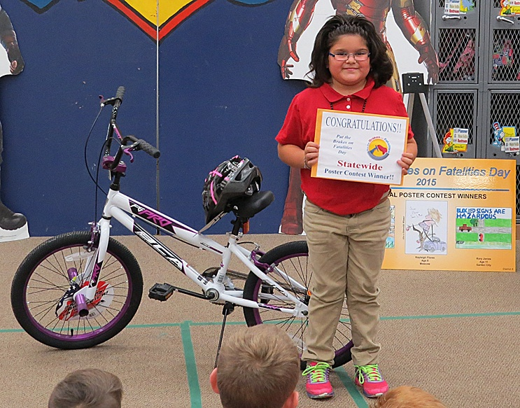 """Young Kayleigh Flores shows off her award-winning poster and her shiny new bike at  Heritage Christian Friday morning. Kayleigh won the bike - and a stay in Kansas City's Great Wolf Lodge - in the """"Put the Brakes on Fatalities Day"""" poster contest recently."""