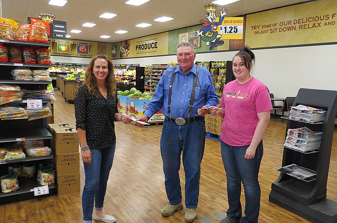 Hugoton Area Chamber Director Alisha Owens hands over $50 in Chamber Bucks to Super Dad 2016 Floyd Knox, while Thrifty King  manager Heather Lane, right, gives him a $25 gift certificate. Floyd has one son and one grandchild. Congratulations and enjoy your winnings!