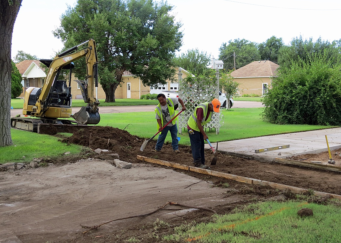 Workers attempt to smooth out a section of a driveway for the Safe Routes to School project currently under construction. The project is expected to be complete by next week.