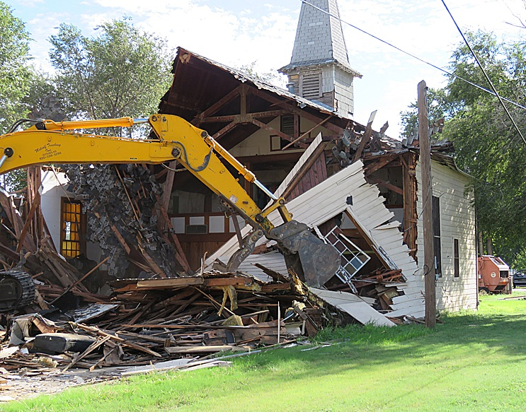 The old Catholic Church interior can be seen as the back half of the building is gone. The crane tears down the walls working towards the front of the building.