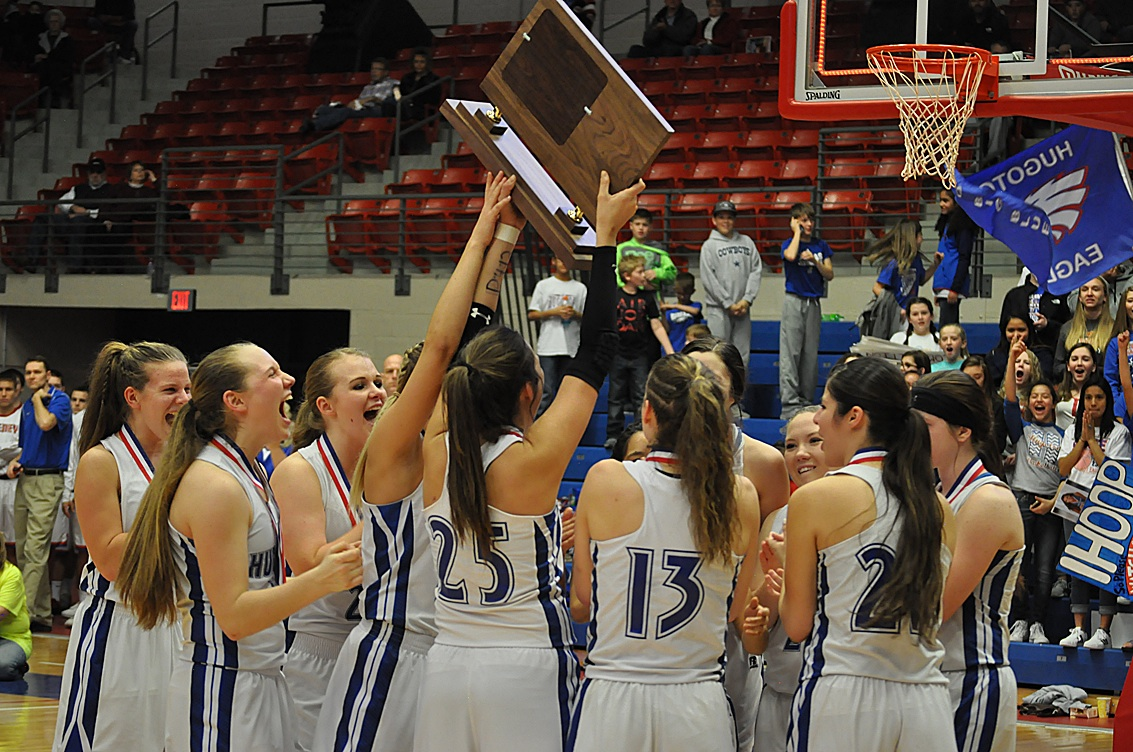 Hugoton's varsity Lady Eagles hoist their 3A State  Championship plaque high in the air after winning over the Cheney Cardinals in Saturday's final game. The Lady Eagles dominated from the very beginning, allowing Cheney's offense only two points in the first quarter, compared to HHS's 21. The reigning State Champions will host a meet and greet Sunday.