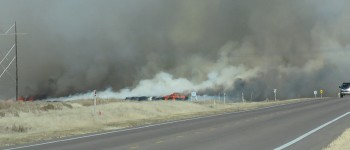 Sunday's wind carries smoke from the fire near Moscow's Northwest Cotton for miles. The gin will record a large loss of cotton, but fortunately there were no injuries reported. Many people helped by donating time, drinks and Hugoton's Pizza Hut even donated pizzas! Area fire departments also helped out with equipment and expertise.