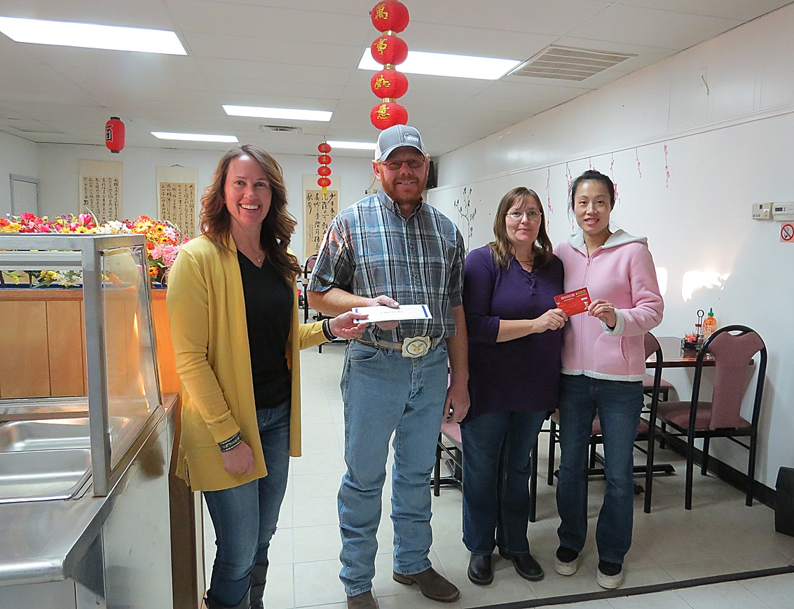 Sweetheart Sweepstake winners Jake and Annie Klassen are handed their awards by  Alisha Owens, Hugoton Area Chamber of Commerce Executive Director at left and Jeney Zhang owner of China Restaurant at right where the couple's names were drawn.